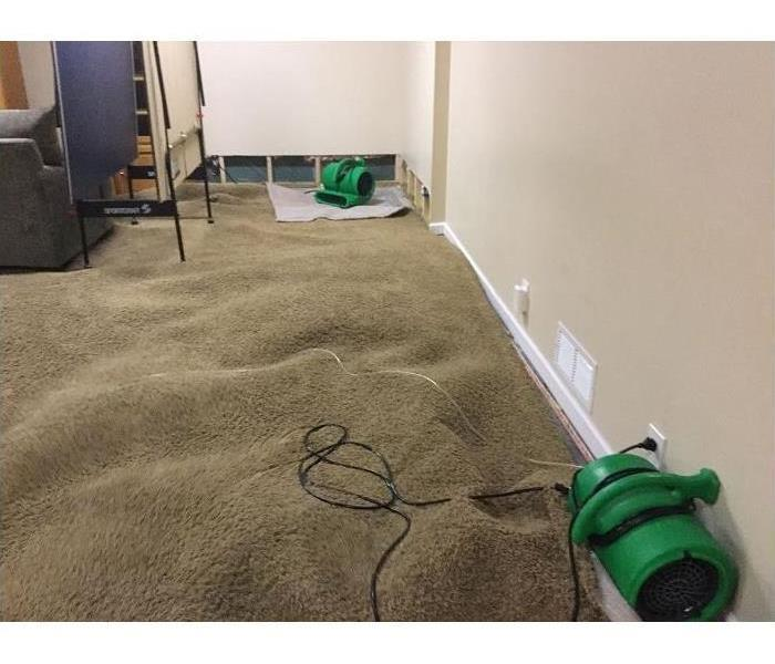 Water Damage in basement, carpet pulled up for drying.