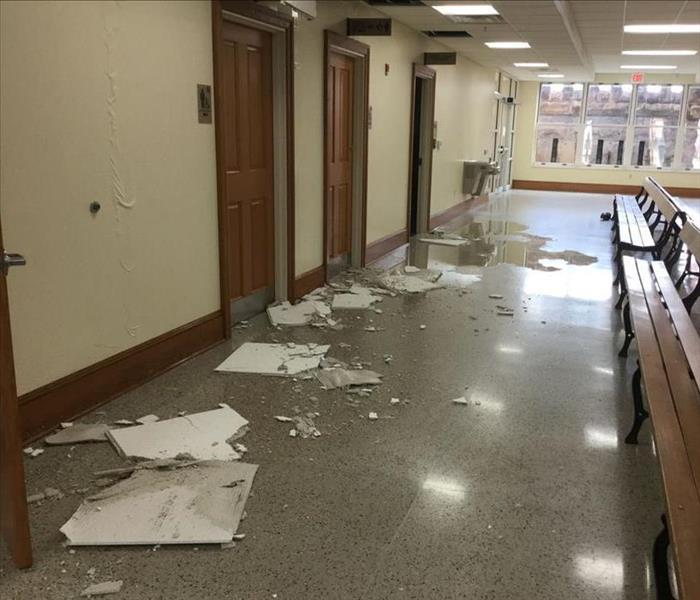 Water damaged walls, ceiling tiles fallen throughout a hallway in the courthouse from water.