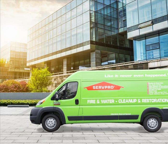 SERVPRO vehicle parked in front of glass buildings in a city atmosphere.