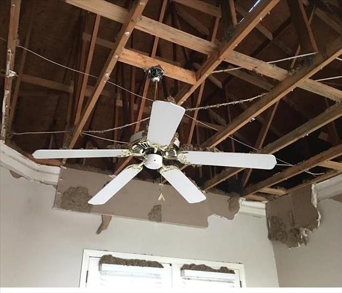 Living-room ceiling that has collapsed from strong rain and storms. One white ceiling fan remains hanging from the ceiling.