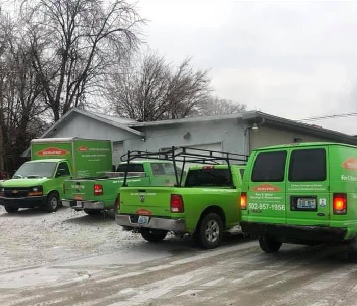 4 SERVPRO trucks located in front of grey commercial building, light snow covering parking lot