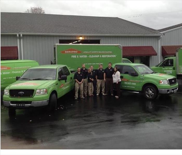 Grey commercial building, red awnings, 5 SERVPRO vehicles, 7 SERVPRO employees